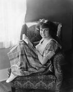 Portrait of a young woman sitting in an armchair and holding a book Stock Photos