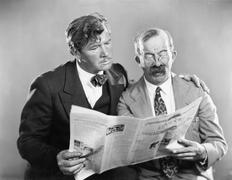 Two mature men reading a newspaper together - stock photo