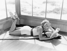 Profile of a young woman lying on a blanket on her stomach and reading a book Stock Photos