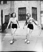 Two young women roller skating on the road and smiling Stock Photos