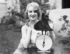 Portrait of a young woman weighing her puppy on a weighing scale Stock Photos
