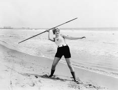 Young woman preparing to throw a javelin on the beach Stock Photos