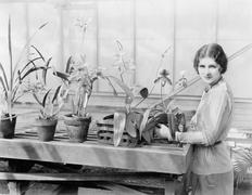 Portrait of a young woman attending to her orchids Stock Photos