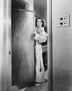 Portrait of a young woman standing at a door of a bathroom Stock Photos