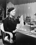 Young woman sitting in a department store and holding stockings Stock Photos