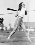 Young woman swinging a baseball bat in a baseball field Stock Photos