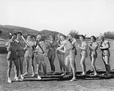 Ryhmä naisia, joilla pesäpallomailat ja seisoo rivissä Kuvituskuvat