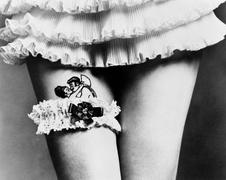View of a woman hiding a tattoo with a garter on her thighs Stock Photos