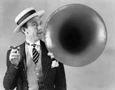 Man holding a cigar and standing near a victrola horn Stock Photos