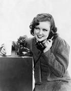 Young woman holding a glass of milk and talking on a rotary phone Stock Photos