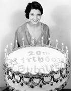 Portrait of a young woman standing in front of a birthday cake - stock photo
