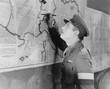 Soldier looking at a map marking it with a pen - stock photo