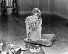 Nainen polvillaan tyynyn katsomalla revitty kuva mies Kuvituskuvat