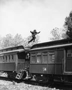 Man leaping across the roof of railroad cars Stock Photos