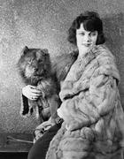 Woman in her fur coat sitting with her dog Stock Photos