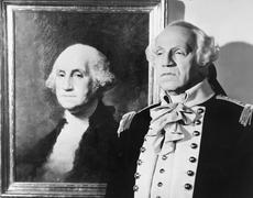 Portrait of George Washington with an impersonator next to the image - stock photo