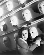 Woman looking frightened holding onto one mask on the wall of masks Stock Photos