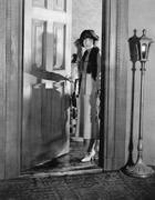 Woman dressed up standing in the doorway - stock photo