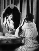 Woman fixing her long hair at her vanity table Stock Photos
