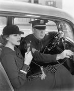 Nainen istuu vieressä poliisi hänen autonsa tilalla mikrofoni kädessään Kuvituskuvat
