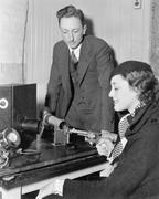 Woman holding a handgun shooting into a tremor machine Stock Photos