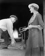 Woman weighing a piece of iron at a foundry - stock photo