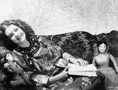 Woman in a Chinese print dress lying on the sofa with her dolls and a book Stock Photos