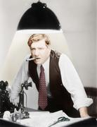 Man leaning over a desk with a ceiling light shining on him Stock Photos