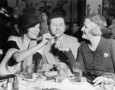 Two women lighting a cigarette for a man - stock photo