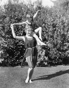 Mother and daughter doing acrobatics in the back yard - stock photo