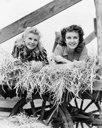 Two women lying in a wagon of hay with their legs in the air Stock Photos