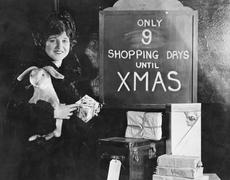 Woman with gifts and sign with number of shopping days until Christmas - stock photo