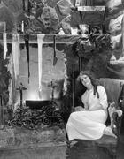 Young woman sitting in front of a fireplace, drying her stockings Stock Photos