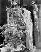 Young woman decorating a Christmas tree Stock Photos