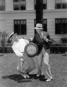 Two men wrestling with an oversized pocket watch Stock Photos