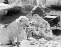 Girl and her dog having a picnic - stock photo