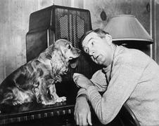 Man and dog listening to the radio Stock Photos