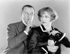 Man telling a woman to be discrete when she is on the telephone - stock photo
