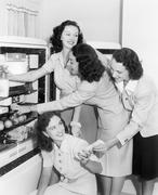 Four women taking things from a refrigerator - stock photo