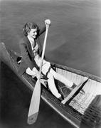 Young woman in a canoe rowing Stock Photos