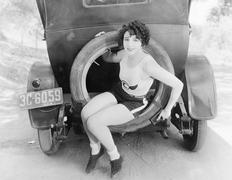 Young woman sitting in the extra wheel of a car Stock Photos