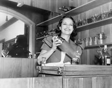 Young woman with a shaker in a bar - stock photo