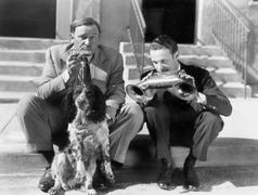 Two men playing two harmonicas with an English Setter Stock Photos