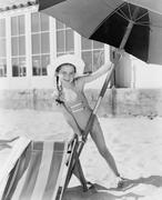 Girl placing a large umbrella into the sand Stock Photos