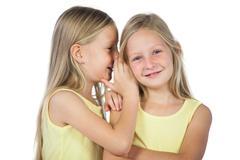 Blonde girl whispering to her sister - stock photo