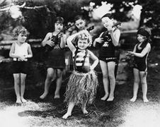 Group of children performing with instruments and one girl dancing the hula Stock Photos