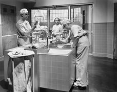 Two surgeons and a nurse in the scrub room preparing for an operation Stock Photos