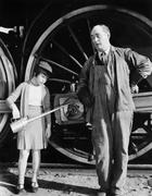 Little girl with an oil can standing next to a locomotive and the engine driver Stock Photos