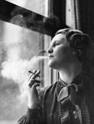Young woman sitting next to window, smoking Stock Photos