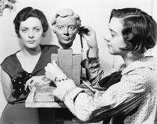 Women and an artist standing together while one is working on a bust - stock photo